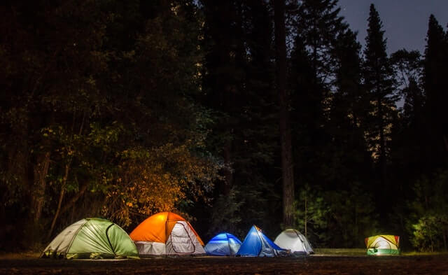 Campsite at night time with multiple campers