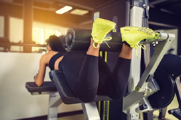 Woman demonstrating good foot position on a hamstring curl machine