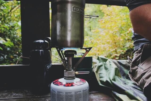Using a propane canister with burner to make coffee.